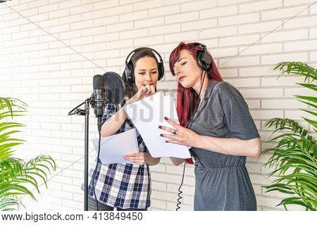 Young Women In Headphones Discussing Script While Standing Near Microphone Against Brick Wall In Fil