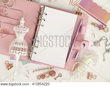 Top View Of A Pink Planner With Cute Stationery. Pink Glamour Planner With A White Mannequin Figurin