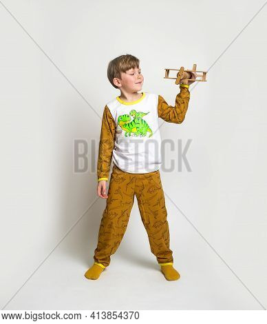 Little Boy In Pyjamas With Wood Toy Plane. Yawning Blond Kid In Pyjamas With Dinosaur Animals Patter