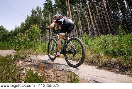 Athlete Cyclist Biking Forest Trail On Mountain Bike