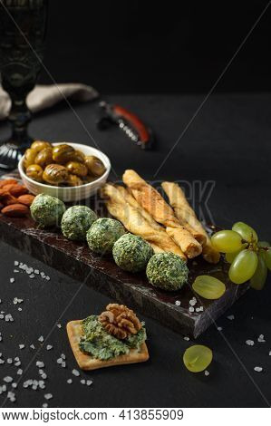 A Set Of Wine Snacks On A Marble Stand. Cheese And Spinach Balls, Dried Olives, Breadsticks And Salt