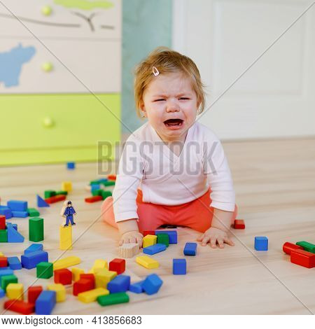 Upset Crying Baby Girl With Educational Toys. Sad Tired Or Hungry Alone Healthy Child Sitting Near C