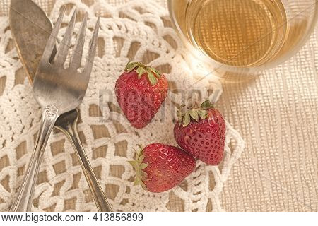 A Concept Photo Of Three Strawberries And Old Tarnished Silverware.