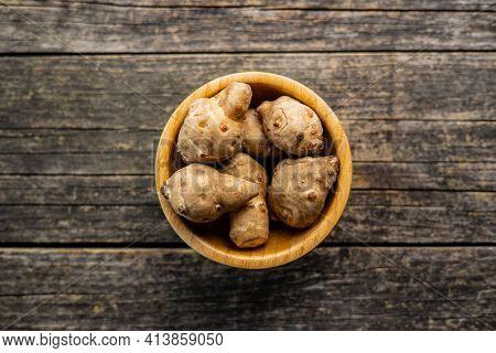 Raw jerusalem artichoke. Topinambur vegetable root in wooden bowl. Top view.
