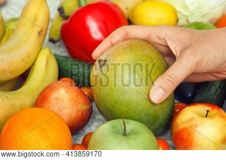 A Woman Taking A Mango Out Of A Pile Of Fruit And Vegetables. Close Up.