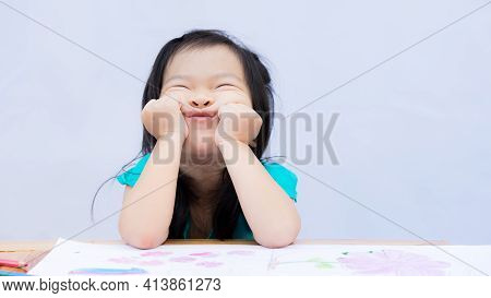 Cute Girl Put Her Two Hands On Her Chin When She Was Bored With Homework. Art Notebook Sits On Table