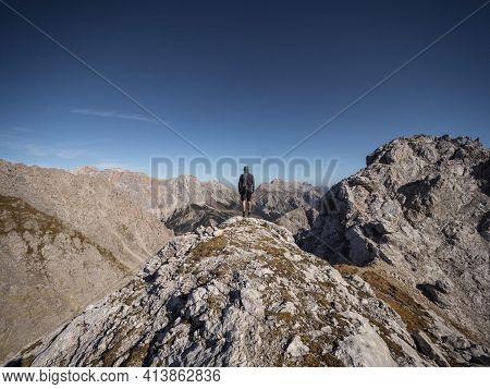 Autumn Fall Landscape Panorama Of Young Male Hiker Standing On Alpine Mountain Summit Tajakopf At La
