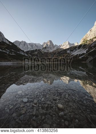 Mirror Reflection Of Autumn Fall Sunset Panorama In Clear Calm Transparent Alpine Mountain Lake Seeb