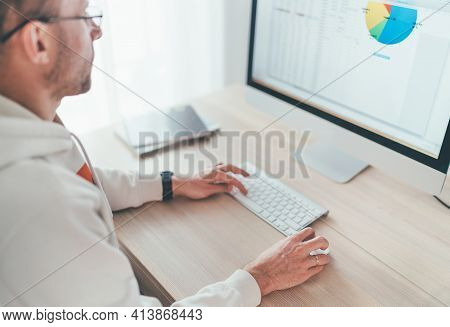 A Middle-aged Man Relaxing On A Swivel Chair Near The Table With Computer While He Watching Tv In Li