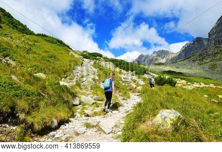 Hikers on trip in Mengusovska Valley, Vysoke Tatry (High Tatras), Slovakia. Mountain landscape in the Western Carpathians.