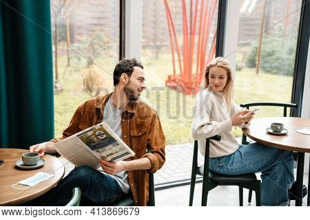 Pleased man and woman using cellphone and reading newspaper while talking in cafe