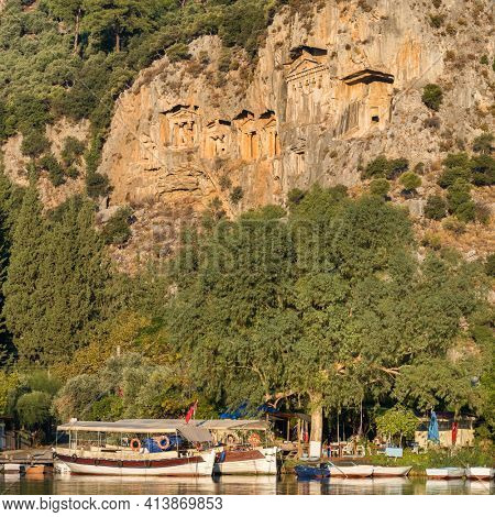 Rock-cut temple tombs of the ancient city Kaunos in Dalyan, Mugla, Turkey. Beautiful Dalyan river view with ferry boats and carved tombs at background.