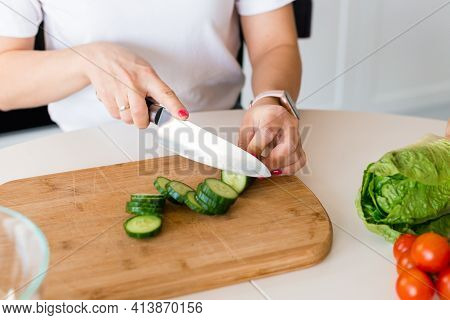 Brunette Woman In White T-shirt Preparing Vegetable Salad In The Kitchen At Home, Wife Cutting Cucum