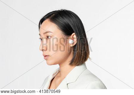 Businesswoman with smart wireless earbuds futuristic communication