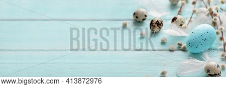 spring banner background with easter quail eggs and willow branches on blue background. copy space for text. Horizontal spring background for easter greetings.