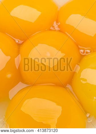 Six bright yellow raw egg yolks in a bowl, close-up.