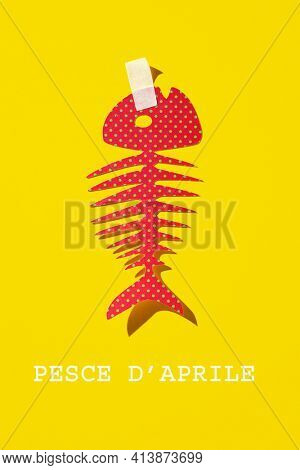 text fish of april written in italian, the equivalent of april fools day in italy, and a homemade paper fish, as a popular prank in this country, where it is typical to attach it to someones back