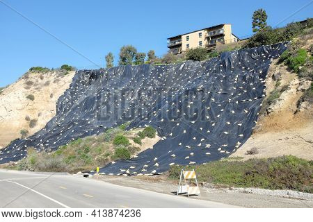 NEWPORT BEACH, CALIFORNIA - JANUARY 16, 2017: Plastic Covered Hillside. Newport Bluffs hillside covered with plastic to prevent erosion. Seen from Back Bay Drive.