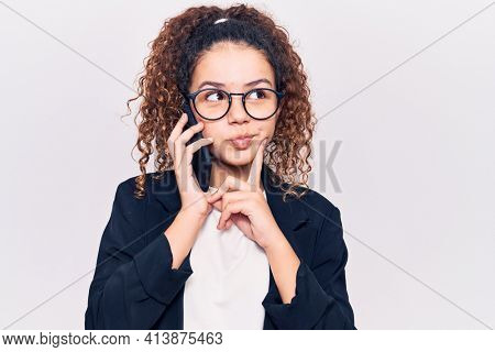 Beautiful kid girl with curly hair wearing glasses having conversation talking on the smartphone serious face thinking about question with hand on chin, thoughtful about confusing idea
