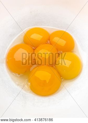 Six bright yellow egg yolks in a white bowl.