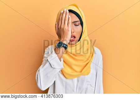 Young brunette arab woman wearing traditional islamic hijab scarf yawning tired covering half face, eye and mouth with hand. face hurts in pain.