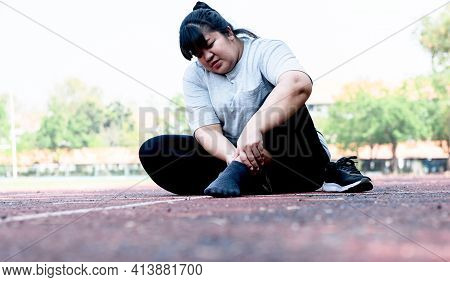 Asian Fat Woman, Is Currently Having A Ankle Injury During Her Exercise By Running In The Running Tr