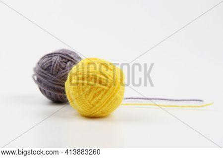 Two Balls Of Yellow And Gray Wool Yarn, Partially Unfolded, For Knitting On A White Background.the C