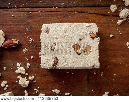 Halva Slice With Almonds On Wooden Table Background, Top View.