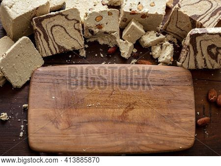 Halva Almond Nuts And Cocoa Slices On Wooden Table Background