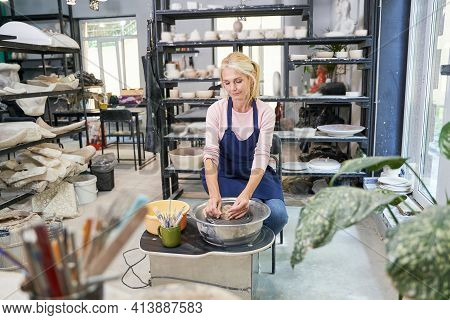 Craftswoman. Relaxed Mature Woman In Blue Apron Looking Focused While Creating Handmade Clay Ceramic