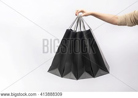 Female Hand Holds Black Paper Shopping Bags Isolated On White Background