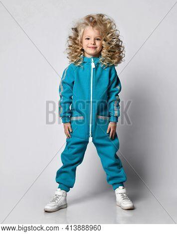 Smiling Girl In Warm Sportswear Fashionable Sportswear Stands In The Studio. Child Beauty Model With