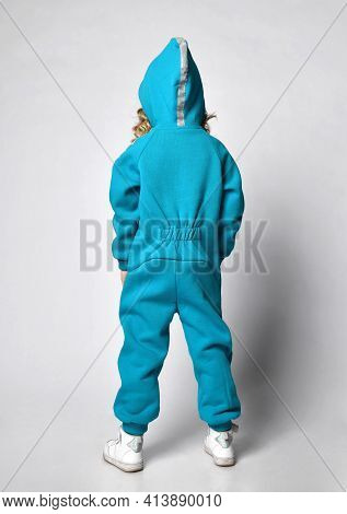 Little Preschooler Or Schoolgirl In A Warm Blue Tracksuit With A Hood And White Sneakers, Full-lengt