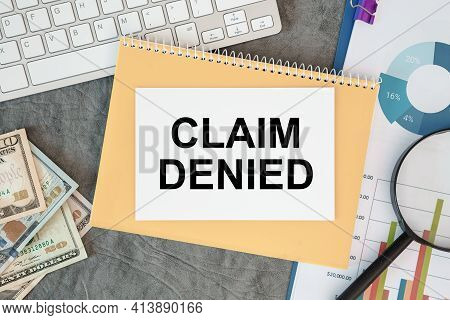 Claim Denied Is Written In A Document On The Office Desk With Office Accessories, Money And Diagram