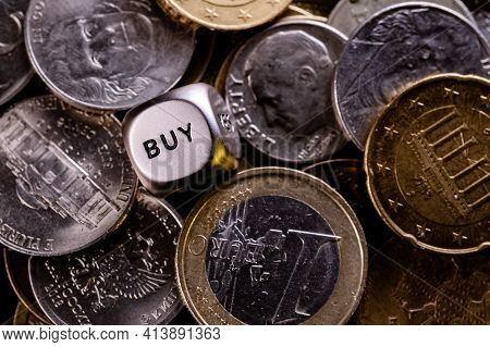 A Metal Dice In A Pile Of Coins From Different Countries. On The Edge Of The Dice Is The Word