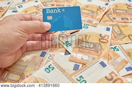 A White Or Caucasian Man Holds In His Hand A Microchipped Credit Or Debit Card On A Background Of Fi