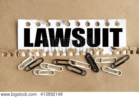 Lawsuit . Text On White Paper Over Torn Paper Background.