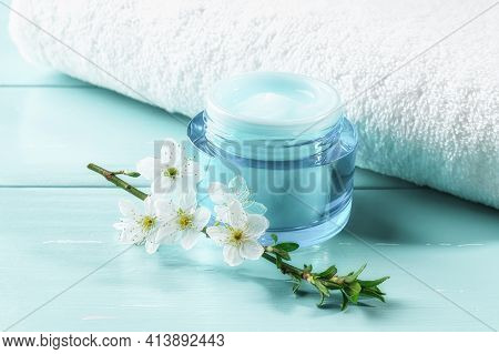 Jar Of Hydrating Facial Gel And Cherry Blossom Near White Towel Over Blue Wooden Surface. Blue Conta