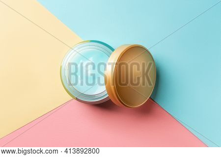 Moisturizing Facial Gel In An Open Jar And Golden Lid Against Blue Pink Yellow Paper Background. Gla