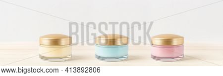 Set Of Three Jars With Moisturizing Facial Cream On A Light Wooden Surface. Glass Container Of Hydra