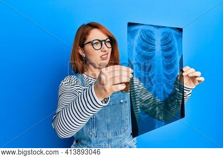 Beautiful redhead woman holding chest radiography clueless and confused expression. doubt concept.