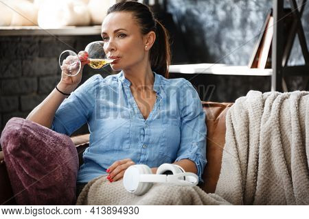 Leisure time concept. Happy beautiful woman drinks white wine from glass sitting on a couch indoors. Female spending her free day and relaxing at home alone