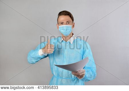 A Fair-haired Male Surgeon In A Blue Uniform, Wearing A Medical Mask And Protective Gloves, Holds Ou