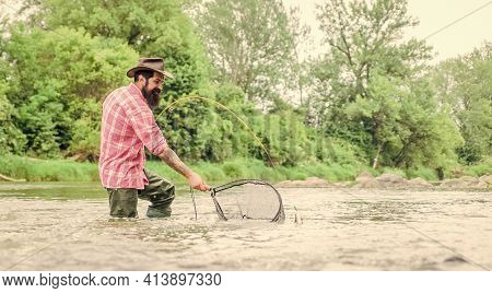 New Skills. Hobby And Sport Activity. Happy Bearded Fisher In Water. Fisherman Show Fishing Techniqu