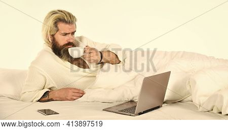 Screen Time And Insomnia. Happy Hipster Drink Coffee In Bed. Bearded Man Enjoy Coffee And Surfing In
