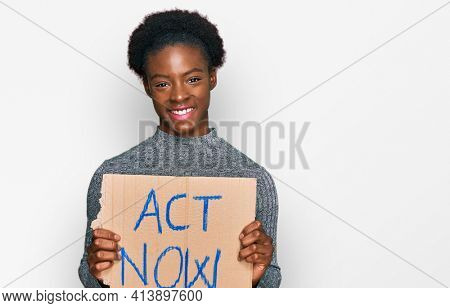 Young african american girl holding act now banner looking positive and happy standing and smiling with a confident smile showing teeth