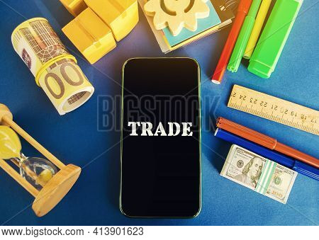 Phone With The Word Trade On A Blue Background With Money, Boxes And Hourglass. Business Market And