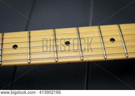 Fretboard Of A Lacquered Electric Guitar, With Bright Strings And Dot-shaped Marks To Identify The N
