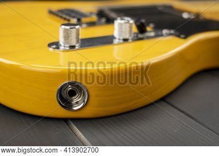 Jack Input Of A Yellow And Lacquered Classic American Electric Guitar With Chrome Metallic Elements