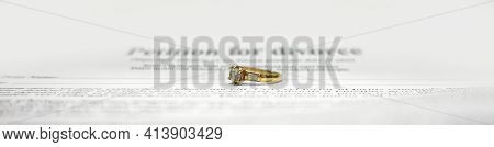 Conceptual Wide Image For Divorce With Two Golden Wedding Ring In The Middle And Petition For Divorc
